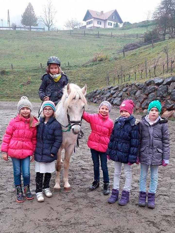 Kinder mit weißem Pferd